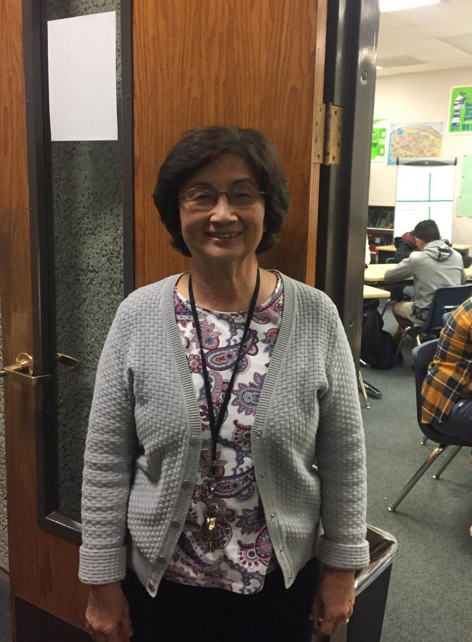 Mrs. Chang in front of her classroom door.