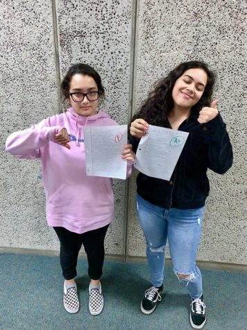 Sophomores Amirah Jabr and Bella Castro showing off their amazing grades they received on a paper.